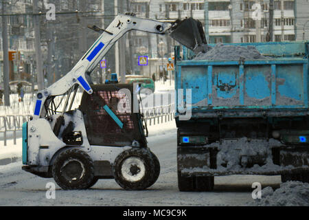 Snow plow removing snow from city road - Stock Photo