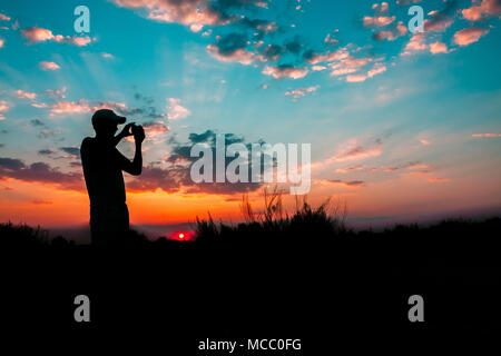 Dark Silhouette Of Young Man Photographing Sunset On Smartphone Camera And Background Of Colourful Evening Sky. Sun Sunshine During Sunrise In Natural - Stock Photo