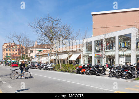 Woman pushing a bicycle in Granviale Santa Maria Elisabetta, Lido, Venice, Veneto, Italy with parked motorbikes in front of shops and restaurants. Bik - Stock Photo