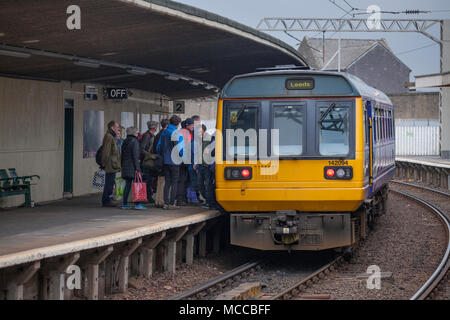 Passengers boarding a Northern Rail pacer train at Carnforth railway station - Stock Photo