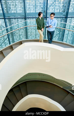 Having Discussion on Spiral Concrete Staircase - Stock Photo