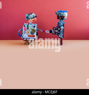 Two robots greet each other. Handshake of cybernetic mechanical cyborgs. Creative design robotic toys, red wall brown floor background. Copy space - Stock Photo