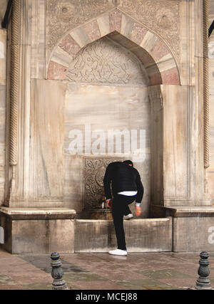 Man cleaning shoes in a public fountain in historical city - Stock Photo