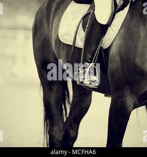 Foot of the athlete in a stirrup astride a horse - Stock Photo