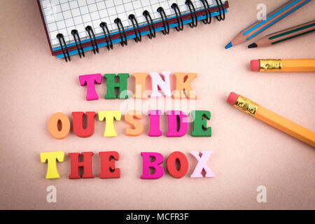 Think outside the box. Wooden letters on the office desk - Stock Photo