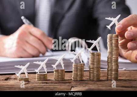 Close-up Of A Human Hand Placing Small Aeroplane On Increasing Stacked Coins Over Wooden Desk - Stock Photo