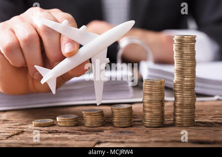 Close-up Of A Businessperson's Hand Flying Aeroplane Over Stacked Coins At Workplace - Stock Photo