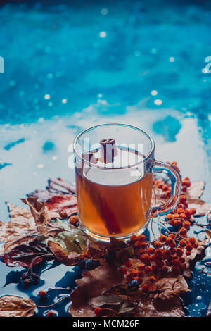 Tea with cinnamon in an autumn still life with fallen leaves and ash berry on a wet wooden background. Seasonal concept with copy space. - Stock Photo