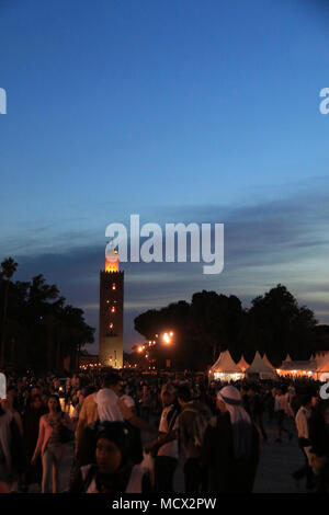 Crowd of people in front of food stalls and the Moroccan tower at the entrance to the famous Jemaa el-Fnaa square in Marrakesh, Morocco - Stock Photo