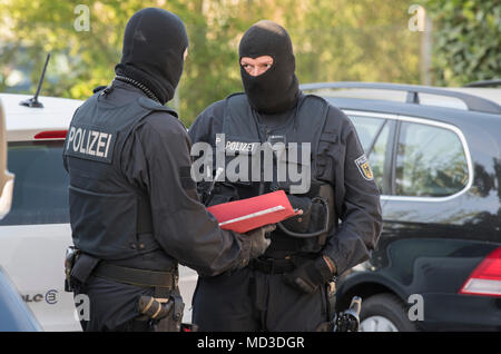 18 April 2018, Rastatt, Maintal: Masked officers of the German police force during a raid of a brothel. The police is cracking down on organized crime in a large-scale, nationwide raid starting Wednesday morning. According to the German police in Stuttgart, the focus lies on forged visas, human trafficking, pimping, and forced prostitution of Thai women. More than 1500 police officers are taking part in this raid. Photo: Boris Roessler/dpa - Stock Photo