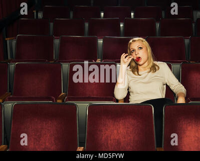 A woman sitting in an old theater sucking on a lollipop. - Stock Photo