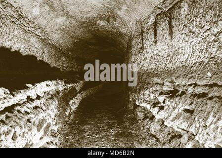 The old sandstone water tunnel, mined caves.  The cave. Sandstone tunnel moistened walls. Dry channel carved in the rocky underground. Solarize effect - Stock Photo