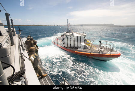 A 47-foot Motor Lifeboat, assigned to U.S. Coast Guard Sector Guam, pulls alongside a Mark VI patrol boat, assigned to Coastal Riverine Group (CRG) 1, Det. Guam, during a towing exercise in Apra Harbor, Guam, March 28, 2018. CRG-1, Det. Guam is assigned to Commander, Task Force 75, the primary expeditionary task force responsible for planning and execution of coastal riverine operations, explosive ordnance disposal, diving engineering and construction, and underwater construction in the U.S. 7th Fleet area of operations. (U.S. Navy Combat Camera photo by Mass Communication Specialist 1st Class - Stock Photo