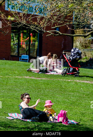 Bolton, UK. April 19, 2018. Glorious sunshine saw the crowds flock to Moss Bank Park in Bolton this afternoon on what is expected to be the hottest day of the year so far. Temperatures are set to reach the mid 20's centigrade and the hot spell is going to last until the weekend. Picnic in the park time for these young families. Picture by Paul Heyes, Thursday April 19, 2018. Credit: Paul Heyes/Alamy Live News - Stock Photo