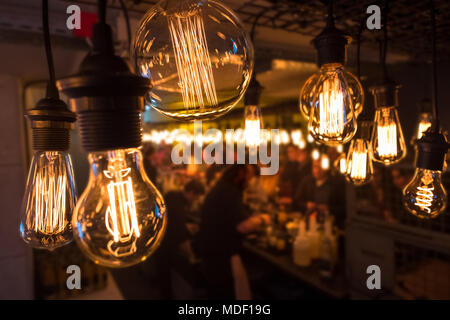 Group of unrecognizable young people during a party standing at the bar in an improvised warehouse environment that could be a school bulding with stylish lightbulbs decoration in the foreground - Stock Photo