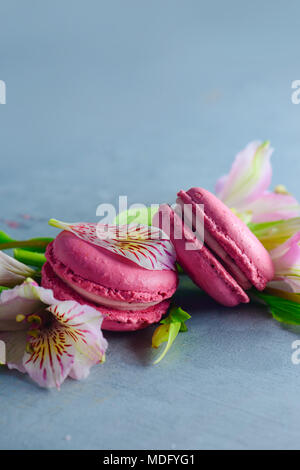 Pink macaroons decorated with pink and white alstroemeria flowers. Romantic French dessert on stone background with copy space. - Stock Photo