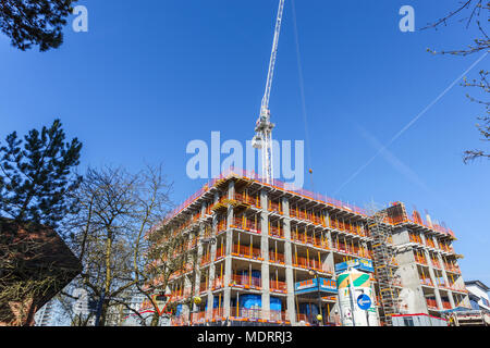 Shell of a new residential apartment block under construction near the railway station and white tower crane, Woking, Surrey, UK on a sunny day - Stock Photo