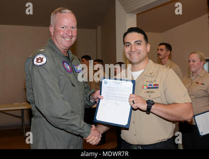 PENSACOLA, Fla. (Dec. 1, 2017)- Naval Air Station (NAS) Pensacola Commanding Officer, Capt. Christopher Martin, presents AC1 Michael Aguilera of Harlingen Tx., with a letter detailing his promotion at a frocking ceremony onboard the base, Dec. 1. (U.S. Navy photo by Gregory Mitchell/NAS Pensacola Public Affairs Office) - Stock Photo