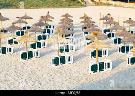 Sunbeds and umbrellas on sandy beach. - Stock Photo