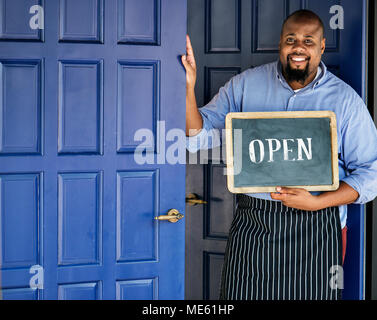 A cheerful small business owner with open sign - Stock Photo