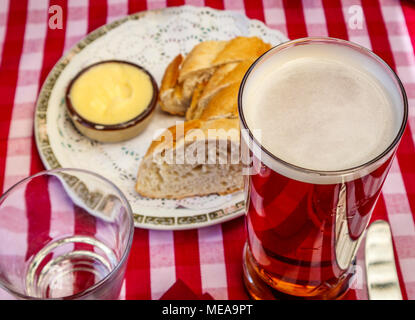 Typical British pub lunch refreshment: a pint of beer in a straight-sided glass with bread and butter on a red and white gingham checked tablecloth - Stock Photo