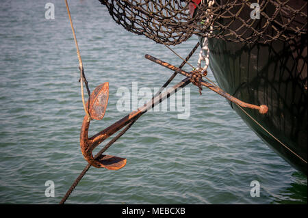 close up of a rusty anchor on the bow of a large barge - Stock Photo