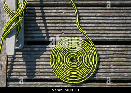 close up of a coil of green rope on a wooden deck with a metal cleat. Boat tied up on a mooring. - Stock Photo