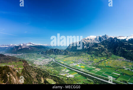 the Rhine Valley near Sargans with lush green fields on the valley floor and snow-capped mountains behind under a blue sky in spring - Stock Photo
