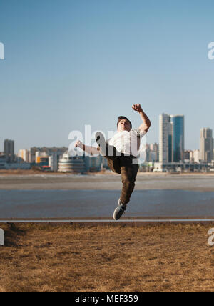 Young male parkour sportsman performs acrobatic jumps in front of skyline - Stock Photo