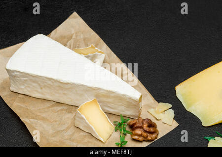 piece of French brie or camembert cheese on concrete background - Stock Photo