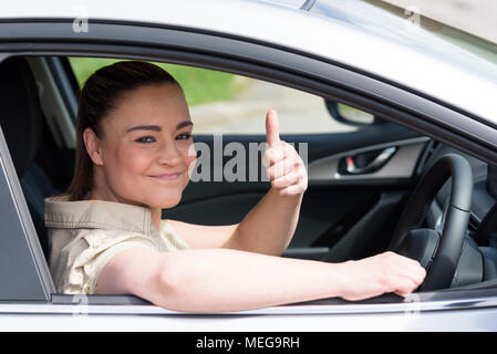 Beautiful young woman driving her brand new car and showing her thumb up - Stock Photo