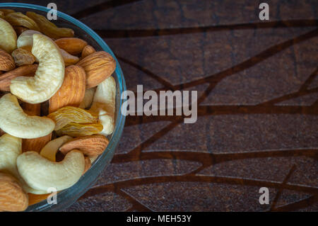 Close up top view of nuts cashew almonds raisins in a bowl on wooden table space for text - Stock Photo
