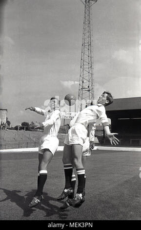 1964, Charlton Athletic FC, historical picture showing Charlton players at the Valley leaping with the ball wearing their new football kit. Between 1964 and 1966 the Charlton players wore a smart all white kit with red shoulders and the hand and sowrd badge first appeared on the shirt. - Stock Photo