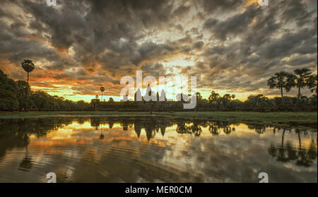 Cambodia ancient Temple Complex Angkor Wat at sunrise with dramatic clouds over the towers and reflection in the pond. Famous travel destination. - Stock Photo