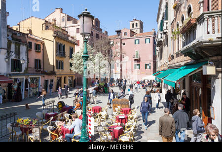Campo Santa Maria Nova in spring, Cannaregio, Venice, Veneto, Italy, with people eating at an open air restaurant enjoying the sunshine, elevated view - Stock Photo