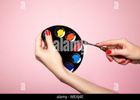 Artist's palette close-up. A palette of colors for painting makeup. Hand with manicure. Spatula artist - Stock Photo