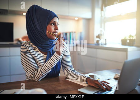 Young Arabic female entrepreneur wearing a hijab looking deep in thought while sitting at her kitchen table working on a laptop - Stock Photo