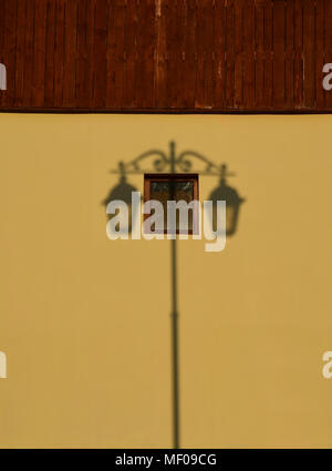 Symmetrical shadow from an old lantern on a yellow brown wall - Stock Photo