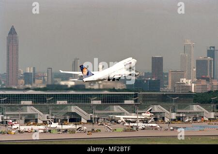 A German Lufthansa Boeing 747 starts on August 23, 1999 from the Frankfurt Rhein-Main Airport, with the skyscrapers in the background and the Messeturm on the left. The particularly clear view and a 600 mm lens allow this perspective.   usage worldwide - Stock Photo