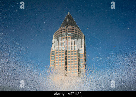Germany, Hesse, Frankfurt, Trade Fair Tower, mirrored in puddle - Stock Photo