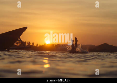 Indonesia, Lombok, man jumping into water - Stock Photo