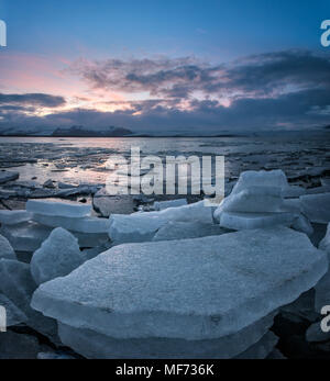 Colorful sunset image of Jokulsarlon Glacier lagoon in Iceland with ice chunks and mountains - Stock Photo