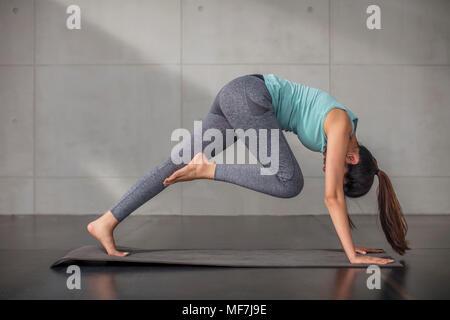 Young woman doing yoga exercise in studio - Stock Photo