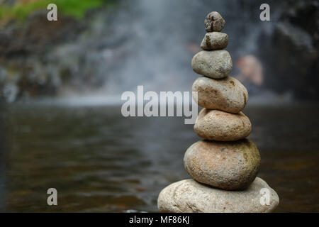 Pebble on the waterfall. The royalty high quality free stock of stones pyramid on pebble waterfall symbolizing stability, zen, harmony, balance - Stock Photo