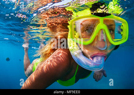 Happy girl in snorkeling mask dive underwater with tropical fishes in coral reef sea pool. Travel lifestyle, water sports, outdoor adventure, swimming - Stock Photo