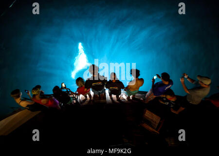 Group of people watch a manta ray swim near surface behind boat to eat plankton at nighttime - Stock Photo