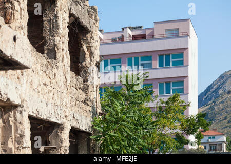 A bombed out building from the Bosnian War next to a new building in Mostar, Bosnia and Herzegovina - Stock Photo
