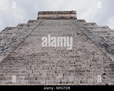 Focus on stairs of Kukulkan pyramid at Chichen Itza mayan town, ruins at most impressive of archaeological sites in Mexico with cloudy blue sky in 201 - Stock Photo
