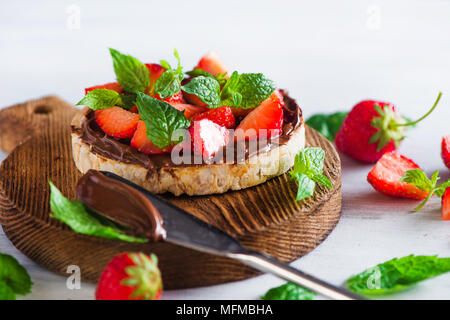 Crisp bread healthy snack with fresh strawberries, chocolate spread, mint leaves on a round cutting board with a dessert knife. Easy breakfast close-u - Stock Photo