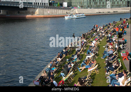 Berlin, Germany: A typical warm weather pastime - people relax in deckchairs, along the banks of the river Spree, on a sunny day. - Stock Photo